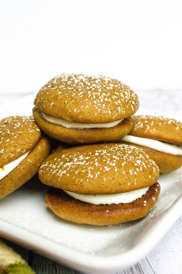 four whoopie pies made with pumpkin on a white plate