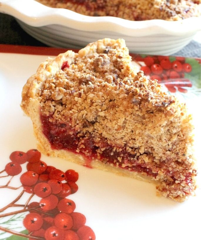 slice of cranberry streusel pie next to a pie plate