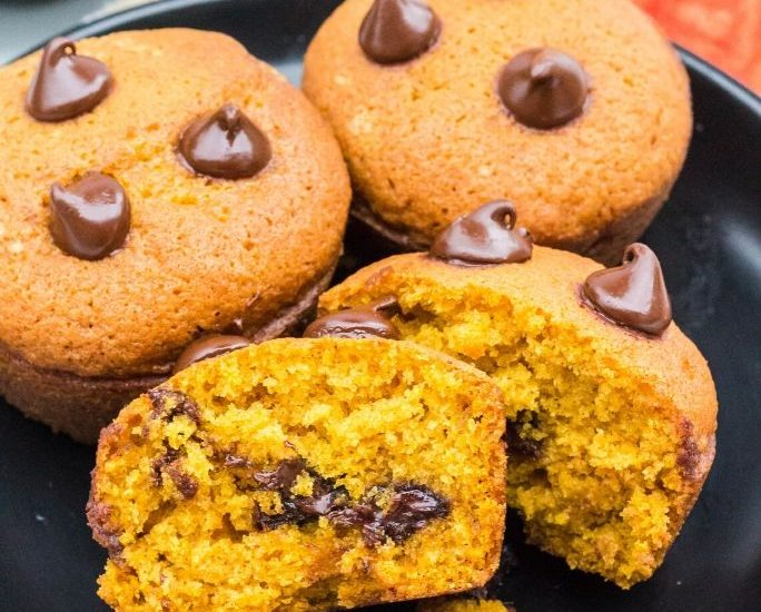 three pumpkin chocolate chip muffins on a black plate, with one muffin cut in half to show the chocolate chips inside