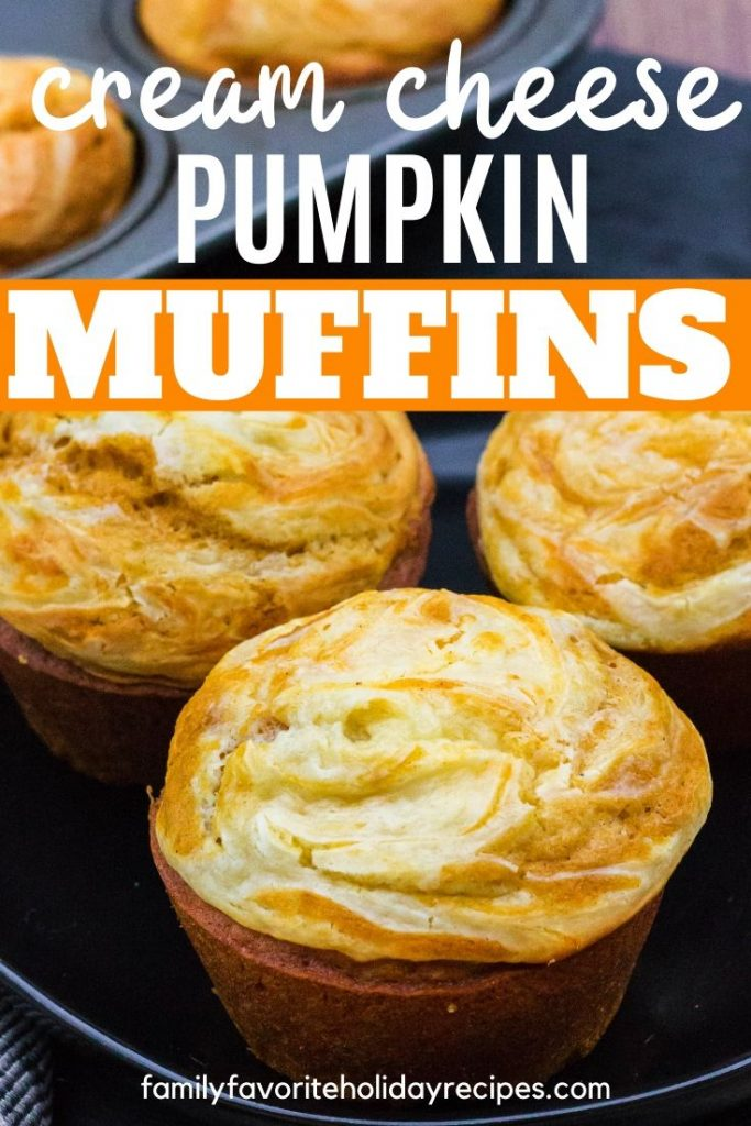 three pumpkin cream cheese swirl muffins in front of a muffin pan
