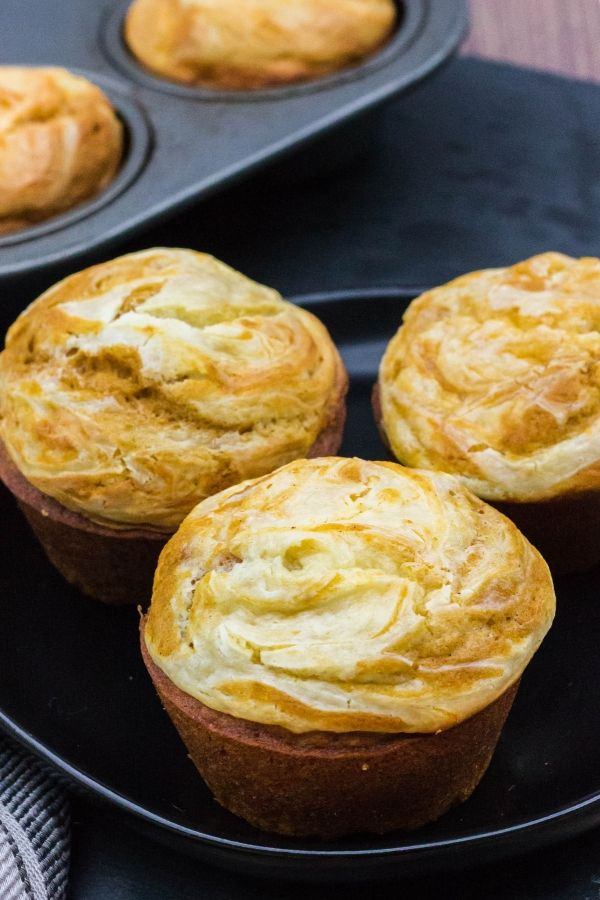 three whole muffins, made with pumpkin and cream cheese, on a black plate