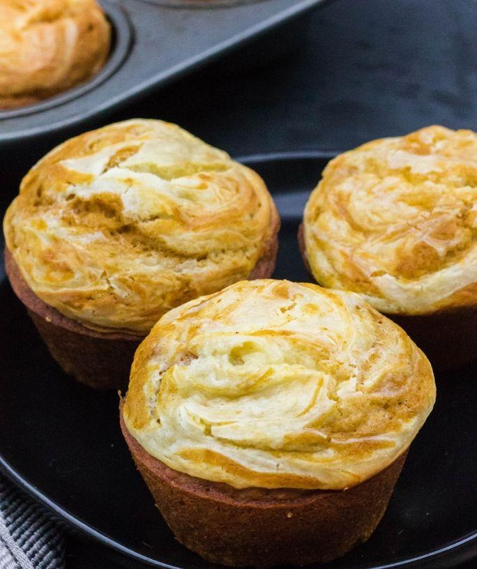 cream cheese swirl pumpkin muffins being served on a black plate