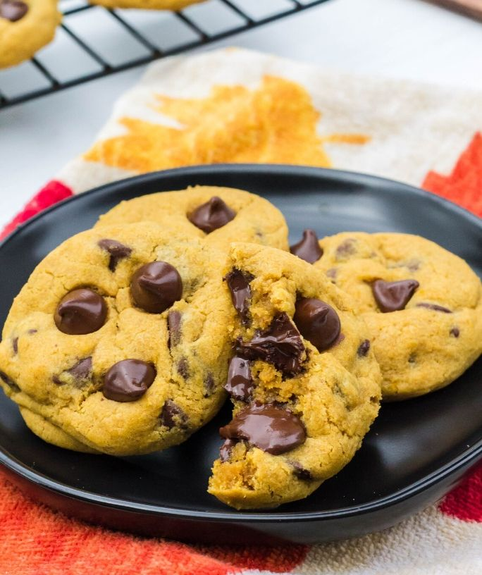 four pumpkin chocolate chip cookies on a plate