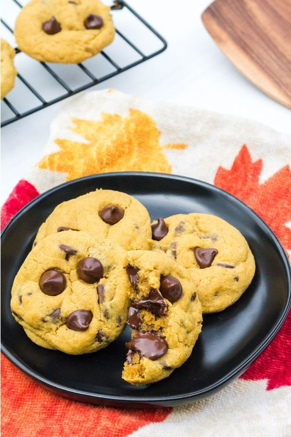 a black plate of pumpkin chocolate chip cookies in front of a cooling rack of cookies