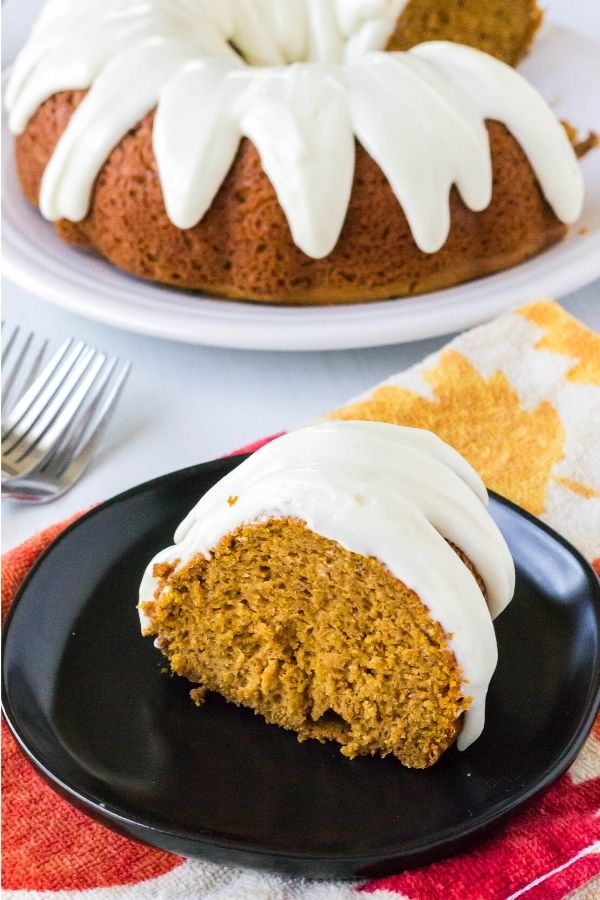 slice of pumpkin spice bundt cake on a black dessert plate, next to the remainder of the whole cake on a serving platter