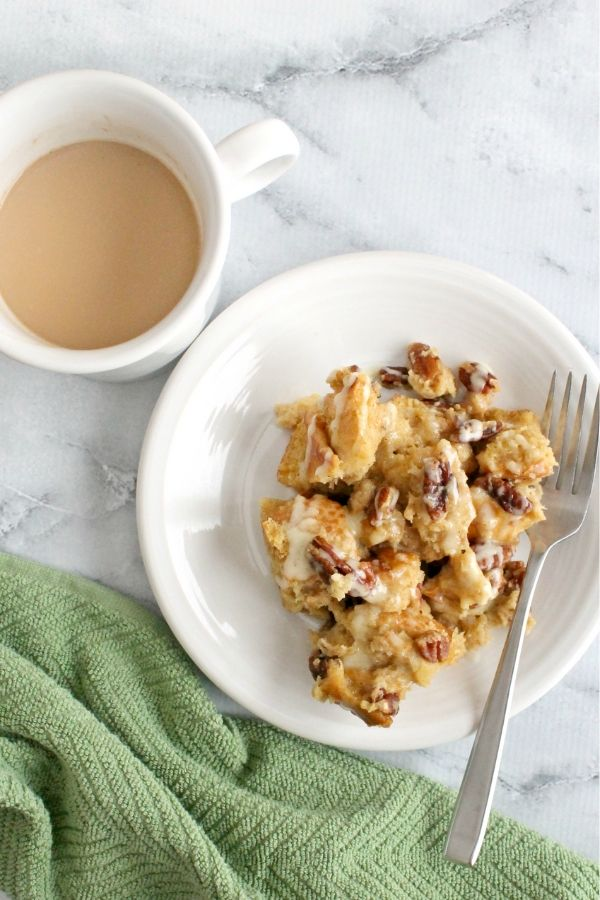 a cup of coffee and a white plate with a helping of overnight eggnog french toast bake on it