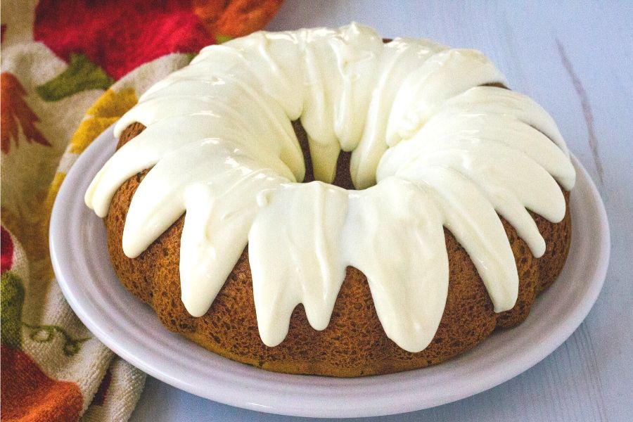 whole pumpkin spice bundt cake on a white serving plate, next to a fall patterned kitchen towel