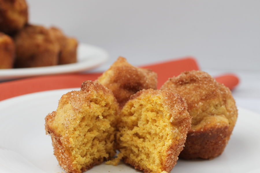 pumpkin cinnamon sugar donut bites on a white plate, with one cut in half to show the moist interior