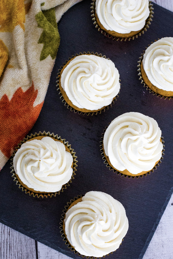 Aerial view of several pumpkin spice cupcakes topped with boiled milk frosting