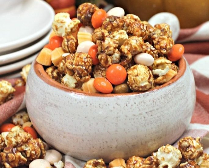 cream-colored bowl filled with pumpkin spice latte popcorn snack mix