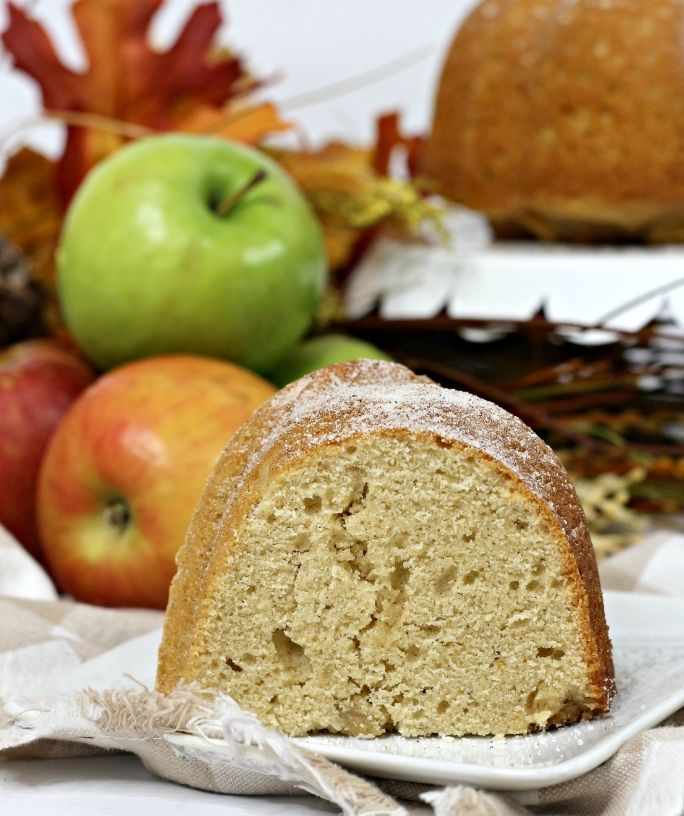 Slice of apple cider bundt cake on a white plate with apples in the background