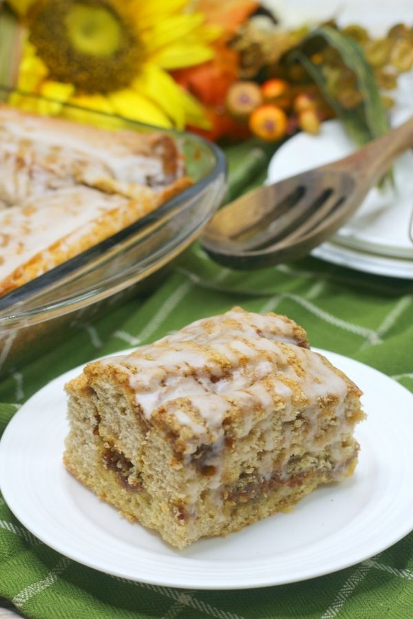 slice of cinnamon roll coffee cake on a white plate, with a green napkin under the plate