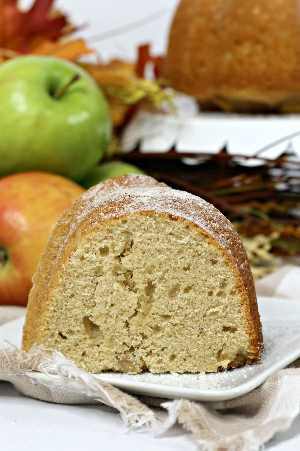 A close-up view of the tender crumb of a slice of apple cider bundt cake, sprinkled with cinnamon sugar