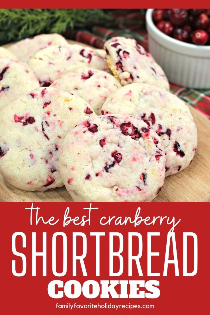 Several shortbread cookies dotted with fresh cranberries and orange zest are served on a wooden board.