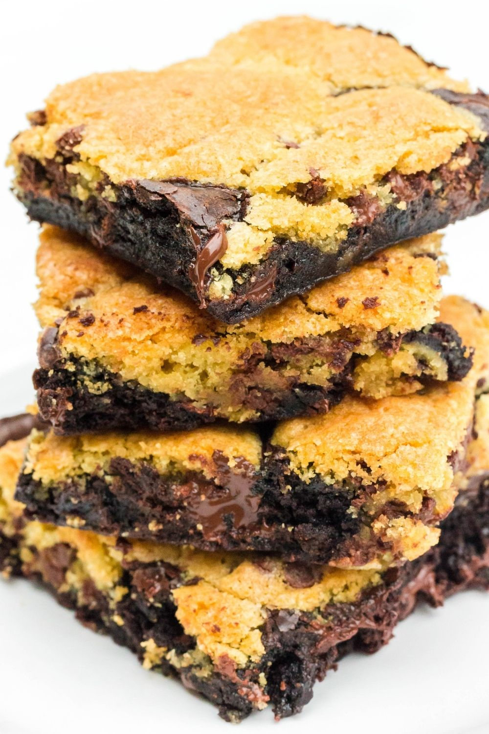 a stack of marbled cookie brownies served on a white plate, showing both the brownie layer and the chocolate chip cookie layers swirled together