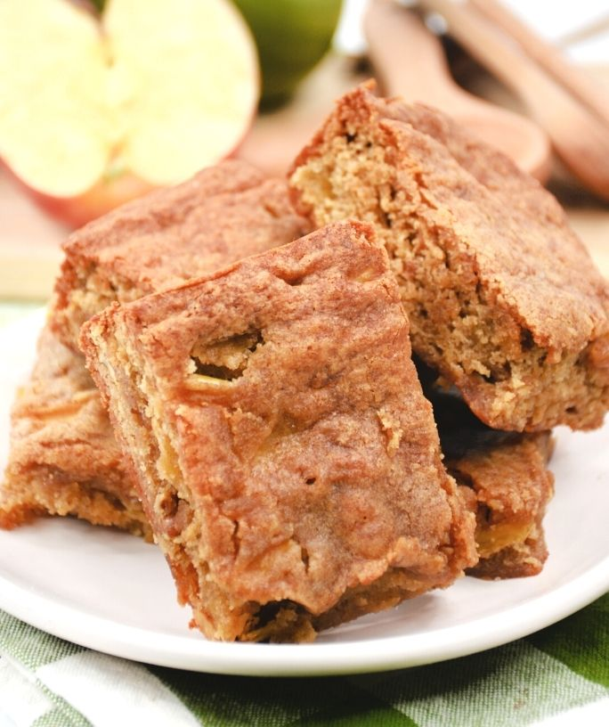 apple blondies on a white plate, with a sliced apple in the background