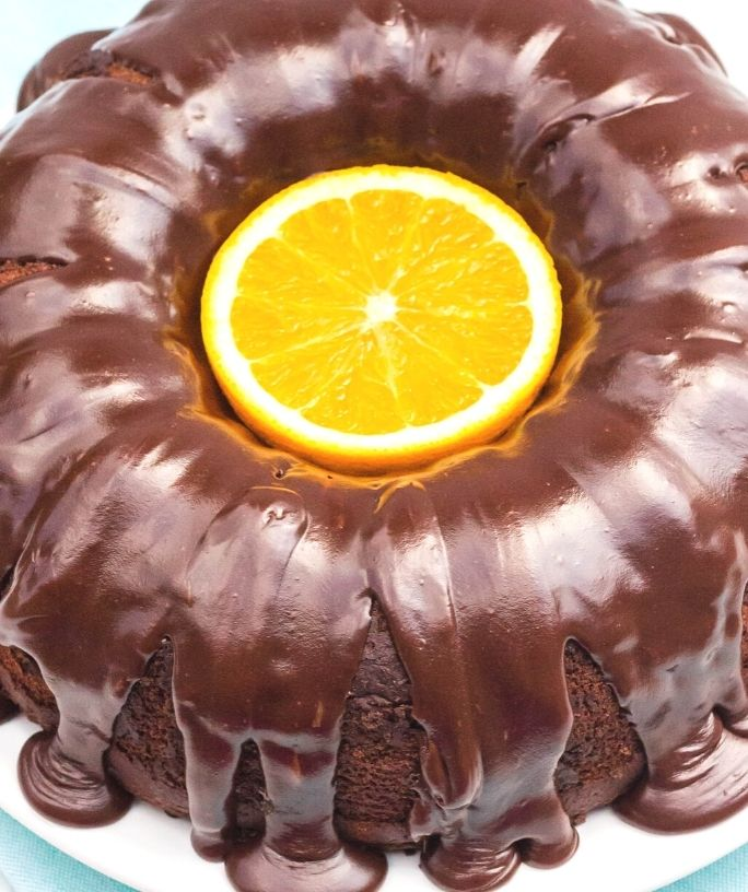 overhead view of a chocolate orange bundt cake with a sliced orange in the center