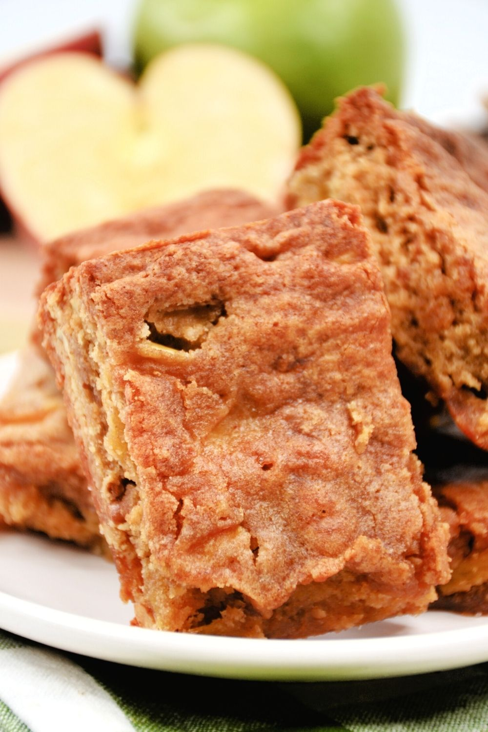 a few apple blondies stacked together on a white plate, with a sliced apple in the background