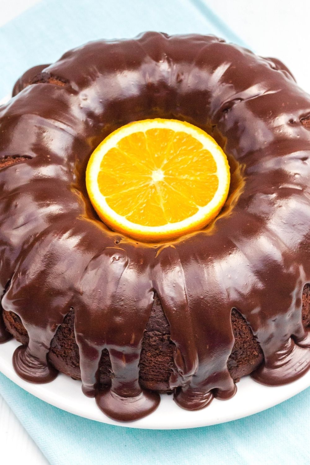 overhead view of a chocolate orange bundt cake with a halved orange in the center for garnish