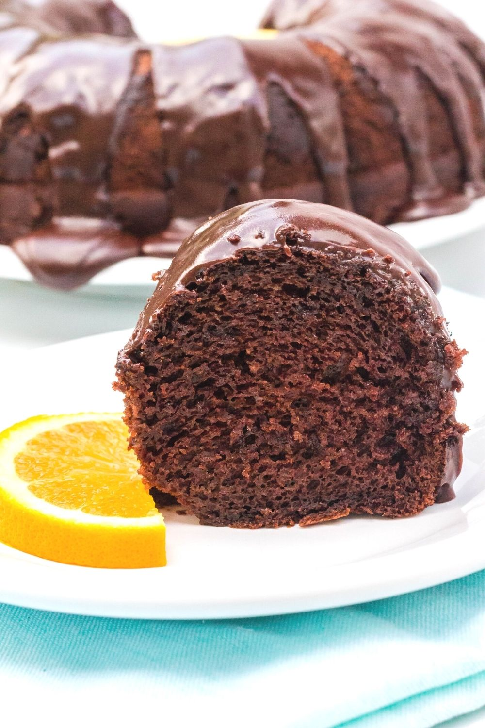 slice of chocolate orange bundt cake on a white plate with a garnish of sliced orange, in front of the remaining whole bundt cake