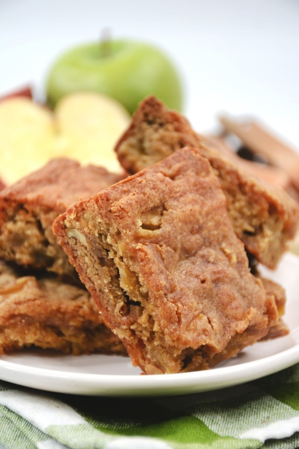 apple blondie bars served on a white plate, atop a green and white checked napkin
